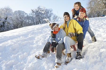 sledging: Famiglia godendo slitta A Snowy Hill