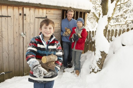collecting: Family Collecting Logs From Wooden Store In Snow