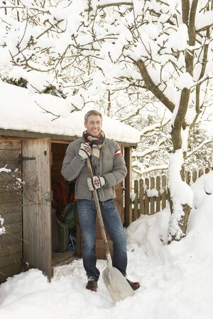 clearing the path: Middle Aged Man Clearing Snow From Path To Wooden Store Stock Photo