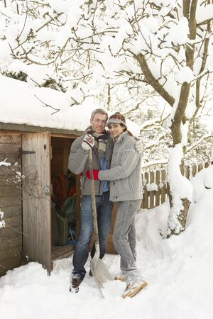 clearing the path: Young Couple Clearing Snow From Path To Wooden Store