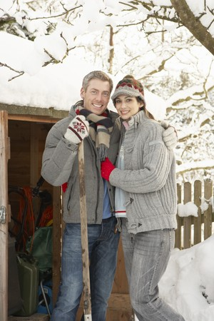 Young Couple Clearing Snow From Path To Wooden Store photo