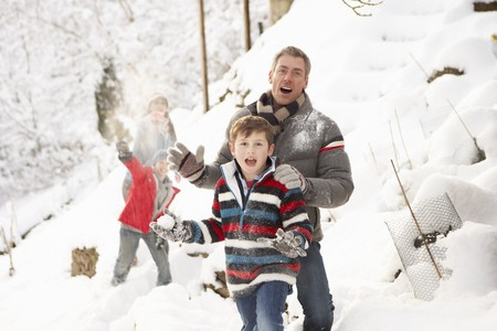 Family Having Snowball Fight In Snowy Landscape photo