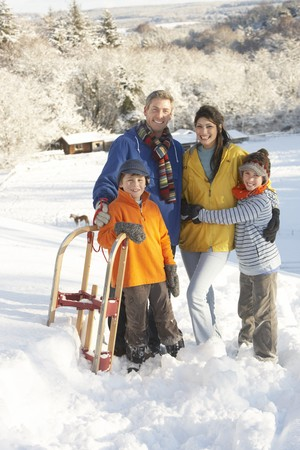 Young Family Standing In Snowy Landscape Holding Sledge Stock Photo - 7178425