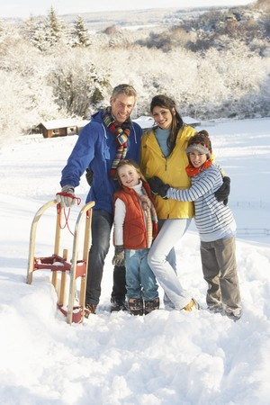 Young Family Standing In Snowy Landscape Holding Sledge Stock Photo - 7178421