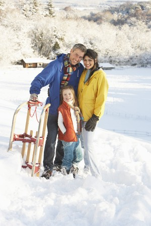 Young Family Standing In Snowy Landscape Holding Sledge photo