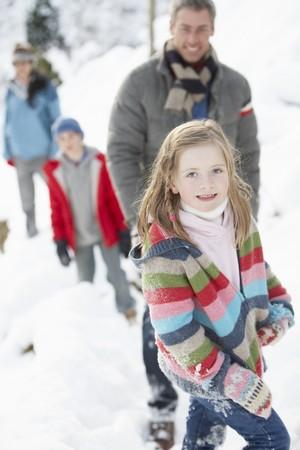 Family Enjoying Walk Through Snowy Landscape photo