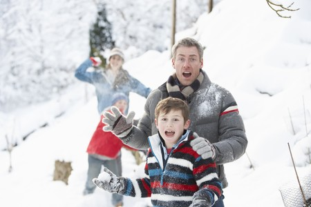 Young Family Having Snowball Fight In Snowy Landscape Stock Photo - 7177176