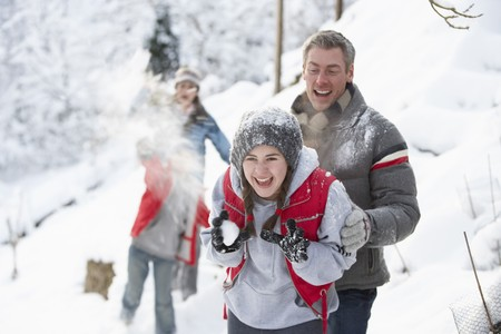 Young Family Having Snowball Fight In Snowy Landscape photo