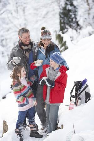Famille arr?t ? chaud de boisson et casse-cro?te on marche dans le paysage Snowy