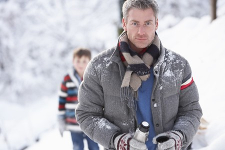 Family Stopping For Hot Drink And Snack On Walk Through Snowy Landscape photo