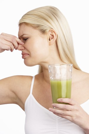 Young Woman Not Enjoying Healthy Drink In Studio photo