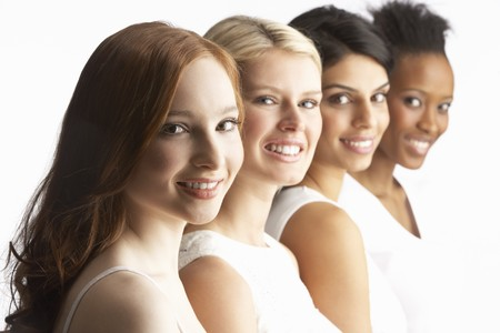 Portrait Of Four Attractive Young Women In Studio Standing In Line Stock Photo