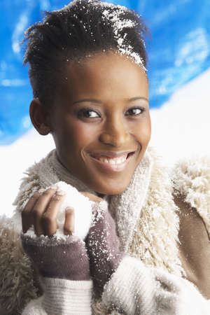 Young Woman Wearing Warm Winter Clothes Holding Snowball In Studio photo