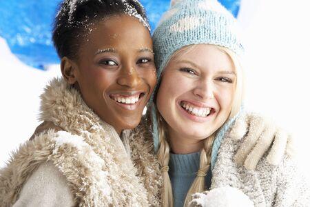 ropa de invierno: Dos mujeres j�venes wearing ropa de invierno c�lido Holding Snowball en Studio