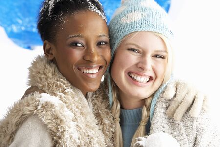 head scarf: Two Young Women Wearing Warm Winter Clothes Holding Snowball In Studio