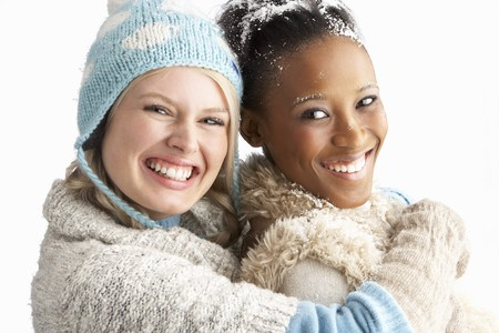 Two Young Women Wearing Warm Winter Clothes Holding Snowball In Studio photo