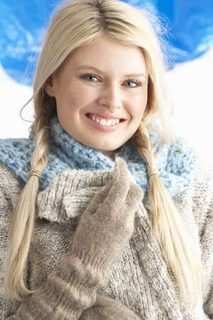 Pretty Young Woman Wearing Warm Winter Clothes In Studio photo