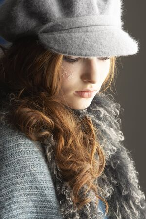 hair wrapped up: Fashionable Teenage Girl Wearing Cap And Knitwear In Studio Stock Photo
