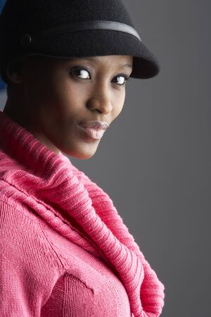 Fashionable Young Woman Wearing Cap And Knitwear In Studio photo