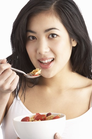 Young Woman Eating Bowl Of Healthy Breakfast Cereal In Studio photo