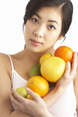 Young Woman Holding Citrus Fruit In Studio photo