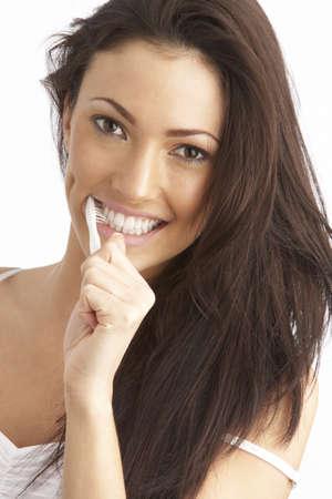 cepillarse los dientes: Mujer joven cepillarse los dientes en estudio