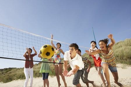 pelota de voleibol: Grupo de amigos adolescentes jugar voleibol de playa