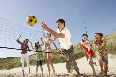 Group Of Teenage Friends Playing Volleyball On Beach Stock Photo