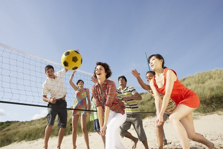 Group Of Teenage Friends Playing Volleyball On Beach Stock Photo - 8452652