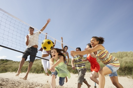 boy friend: Group Of Teenage Friends Playing Volleyball On Beach Stock Photo