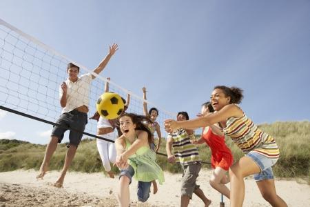 pallavolo: Gruppo di adolescenti amici a giocare a pallavolo sulla spiaggia