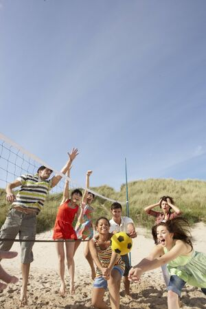 Group Of Teenage Friends Playing Volleyball On Beach photo