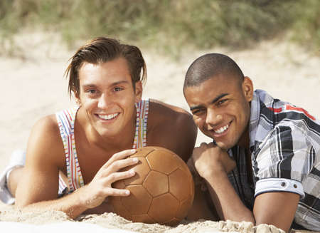Two Young Men Relaxing On Beach With Football Together photo