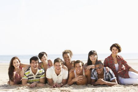 Group Of Friends Sitting On Beach Together Stock Photo - 8453060