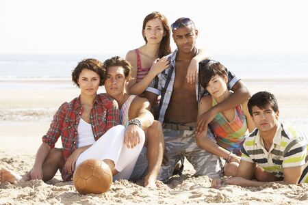 Group Of Friends Relaxing On Beach With Football Together photo