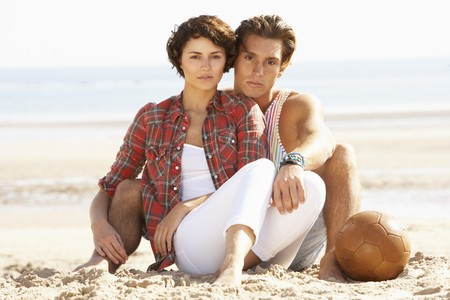 Romantic Young Couple Relaxing On Beach photo