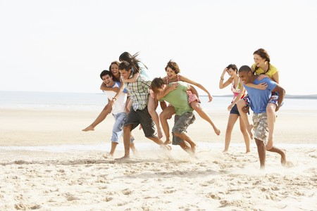 Group Of Friends Running Along Beach Together photo