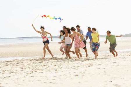 Group Of Friends Running Along Beach Together Banque d'images