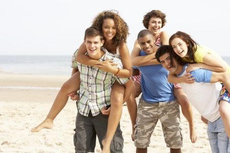 enjoy space: Group Of Friends Running Along Beach Together Stock Photo