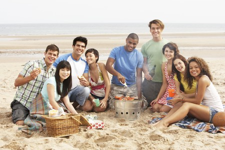 enjoy space: Group Of Friends Enjoying Barbeque On Beach Together