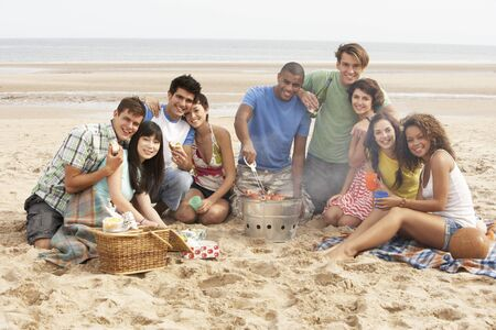 Group Of Friends Enjoying Barbeque On Beach Together photo