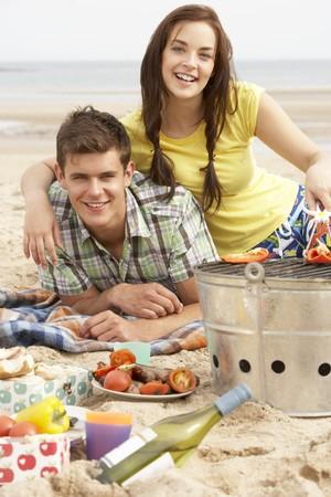 Teenage Couple Enjoying Barbeque On Beach Together photo