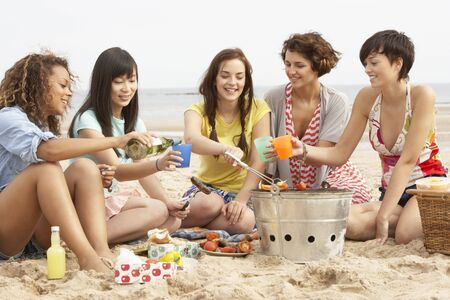 enjoy space: Group Of Girls Enjoying Barbeque On Beach Together Stock Photo