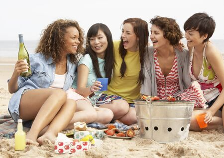 Group Of Girls Enjoying Barbeque On Beach Together photo