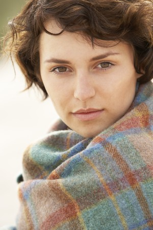 Young Woman Standing In Sand Dunes Wrapped In Blanket photo
