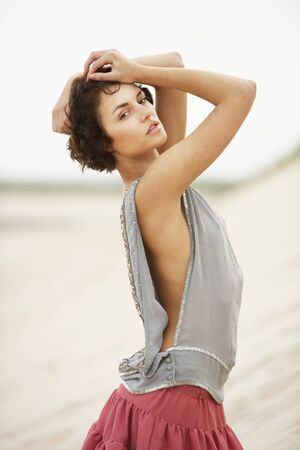 amongst: Attractive Young Woman Wearing Revealing Clothing Standing Amongst Sand Dunes Stock Photo