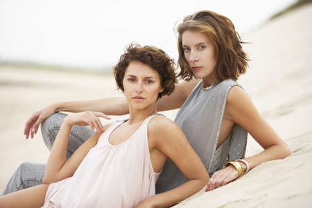 Two Fashionably Dressed Attractive Young Women Laying Amongst Sand Dunes photo