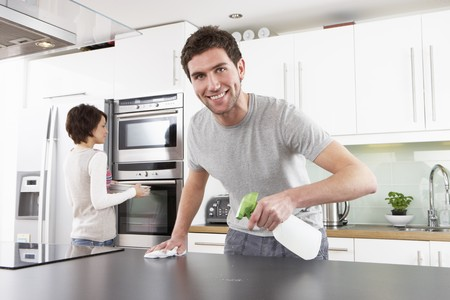 cleaning kitchen: Young Couple Cleaning Cleaning Modern Kitchen