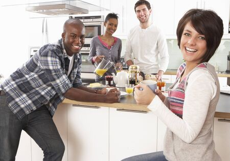 Group Of Young Friends Preparing Breakfast In Modern Kitchen photo