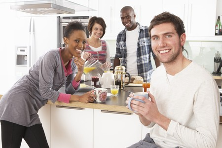 Group Of Young Friends Preparing Breakfast In Modern Kitchen Stock Photo